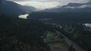 AX154_170 - 6K stock footage aerial video flying over evergreens by Interstate 84 to approach the Bridge of the Gods, Cascade Locks, Oregon in Columbia River Gorge