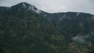 AX154_185 - 6K stock footage aerial video of a rugged mountain cliffs and misty clouds on the Oregon side of Columbia River Gorge