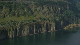 AX154_195 - 6K stock footage aerial video of four waterfalls on steep green cliffs and Columbia River on the Washington side of Columbia River Gorge