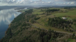 AX154_196 - 6K stock footage aerial video flying over and tilt to Highway 14 through trees by the Columbia River, Washougal, Washington