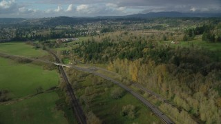 AX154_201 - 6K stock footage aerial video flying over railroad tracks and Highway 14 beside forest near rural homes in Washougal, Washington