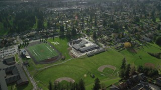 AX154_208 - 6K stock footage aerial video orbiting Gause Elementary, Washougal High School, sports fields, and suburban houses in Washougal, Washington