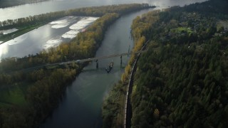 AX154_214 - 6K stock footage aerial video tracking a barge and the Highway 14 bridge over Columbia River to Lady Island, Vancouver, Washington