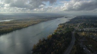 AX154_216 - 6K stock footage aerial video following Highway 14 and the Columbia River toward riverfront homes and the I-205 Bridge in Vancouver, Washington