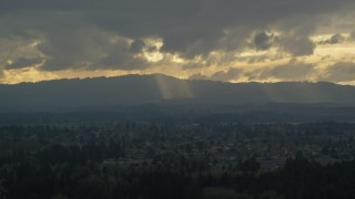 AX155_007 - 6K stock footage aerial video of Cascade Range and godrays shining from clouds seen from suburban neighborhood, Beaverton, Oregon