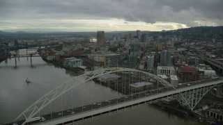 AX155_036 - 6K stock footage aerial video flying by the Fremont Bridge and focus on skyscrapers in Downtown Portland, Oregon