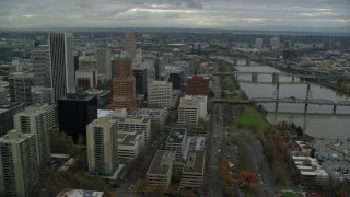 AX155_061 - 6K stock footage aerial video flying by downtown skyscrapers and Hawthorne Bridge spanning the Willamette River in Downtown Portland, Oregon