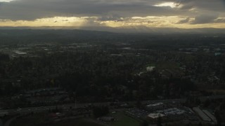 AX155_123 - 6K stock footage aerial video flying by suburban neighborhood with a lot of trees in Beaverton, Oregon, sunset
