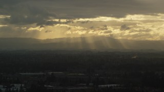 AX155_125 - 6K stock footage aerial video of distant mountains and godrays from the clouds near Beaverton, Oregon, at sunset