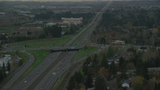 AX155_128 - 6K stock footage aerial video following Highway 26 with light traffic through Hillsboro, Oregon, twilight