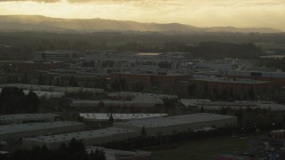 AX155_130 - 6K stock footage aerial video of Intel Ronler Acres with godrays in the background, in Hillsboro, Oregon, sunset