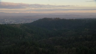 AX155_139 - 6K stock footage aerial video of Mount Hood and Downtown Portland at sunset, seen from forest and hills in Northwest Portland, Oregon