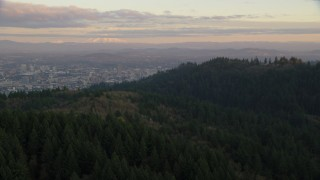 AX155_140 - 6K stock footage aerial video of Mount Hood and Downtown Portland at sunset, seen from evergreen forest and hills in Northwest Portland, Oregon