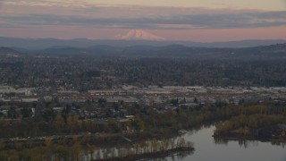 AX155_169 - 6K stock footage aerial video of Mount Hood in the far distance at twilight, seen from a train yard in Southeast Portland, Oregon