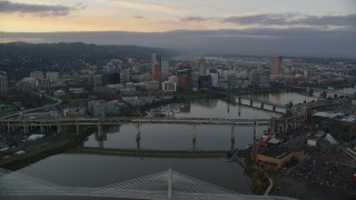 AX155_172 - 6K stock footage aerial video following the Willamette River over bridges to approach Downtown Portland at twilight, Oregon