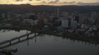 AX155_179 - 6K stock footage aerial video flying over the Willamette River and approach Downtown Portland at twilight in Oregon