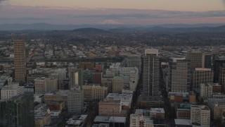 AX155_181 - 6K stock footage aerial video of Mount Hood seen from US Bancorp Tower at twilight in Downtown Portland, Oregon