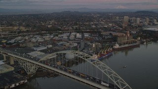 AX155_183 - 6K stock footage aerial video orbiting the Fremont Bridge with very heavy traffic at twilight, to reveal Downtown Portland, Oregon