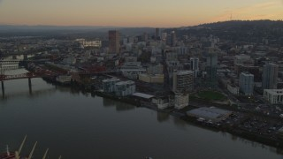 AX155_184 - 6K stock footage aerial video of Downtown Portland skyscrapers and Union Station seen from near the Broadway Bridge at twilight in Oregon