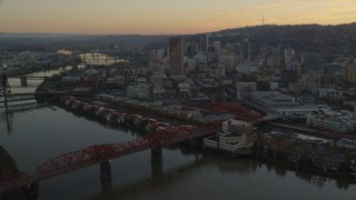 AX155_185 - 6K stock footage aerial video of Downtown Portland skyscrapers and Union Station seen from over the Broadway Bridge at twilight in Oregon