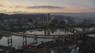 AX155_190 - 6K stock footage aerial video of Downtown Portland skyline seen while flying by Willamette River bridges at twilight, Oregon