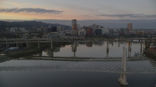 AX155_191 - 6K stock footage aerial video of Downtown Portland skyline and Marquam Bridge seen from Tilikum Crossing at twilight, Oregon