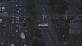 AX155_193 - 6K stock footage aerial video tracking a gondola over I-5 freeway traffic and apartment buildings at twilight, South Portland, Oregon