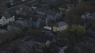 AX155_194 - 6K stock footage aerial video tracking a gondola over apartment buildings at twilight and reveal a second gondola, South Portland, Oregon