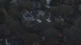 AX155_195 - 6K stock footage aerial video tracking a gondola over apartment buildings and busy streets at twilight, South Portland, Oregon