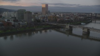 AX155_203 - 6K stock footage aerial video flying over Morrison Bridge, and pass the waterfront park and downtown skyline at twilight, Downtown Portland, Oregon