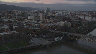 AX155_204 - 6K stock footage aerial video flying over Burnside Bridge, and pass the White Stag sign at twilight, Downtown Portland, Oregon