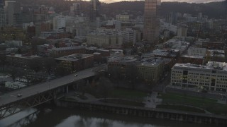 AX155_205 - 6K stock footage aerial video flying by the White Stag sign at twilight, with US Bancorp Tower behind it, Downtown Portland, Oregon