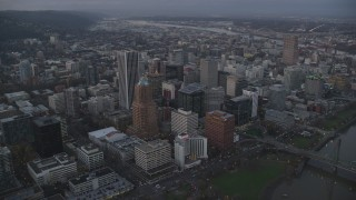 AX155_215 - 6K stock footage aerial video flying over KOIN Center, Wells Fargo Center, and Portland City Hall at twilight, Downtown Portland, Oregon