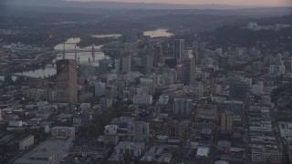 AX155_219 - 6K stock footage aerial video flying by Downtown Portland cityscape by the Willamette River at twilight, Oregon