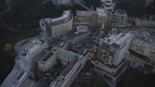 AX155_227 - 6K stock footage aerial video flying by and away from the Oregon Health and Science University in the hills at twilight, Portland, Oregon