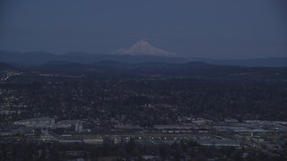 AX155_248 - 6K stock footage aerial video of Mount Hood at twilight, seen from a train yard and neighborhoods in Southeast Portland, Oregon