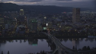 AX155_253 - 6K stock footage aerial video passing skyscrapers and the Morrison Bridge over the Willamette River at twilight, Downtown Portland, Oregon