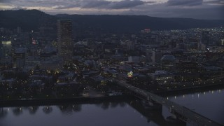 AX155_254 - 6K stock footage aerial video of US Bancorp Tower, Burnside Bridge over the Willamette River, and White Stag Sign at twilight, Downtown Portland, Oregon