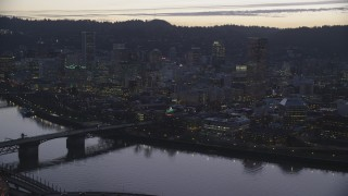 AX155_256 - 6K stock footage aerial video of Burnside Bridge over the Willamette River, White Stag Sign, skyscrapers at twilight, reveal Steel Bridge, Downtown Portland, Oregon