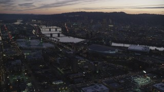 AX155_260 - 6K stock footage aerial video approaching Moda Center, Willamette River, and downtown skyscrapers at twilight, Downtown Portland, Oregon