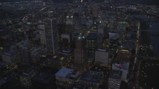 AX155_267 - 6K stock footage aerial video flying away from KOIN Center and Downtown Portland cityscape beside the Willamette River at twilight, Oregon
