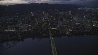 AX155_270 - 6K stock footage aerial video crossing Hawthorne Bridge to approach Downtown Portland's skyscrapers at twilight, Oregon