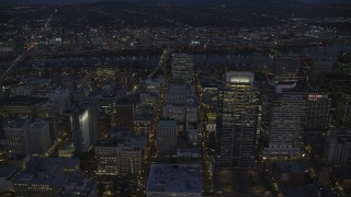 AX155_273 - 6K stock footage aerial video flying by Park Avenue West Tower in downtown, and reveal US Bancorp Tower at night in Downtown Portland, Oregon