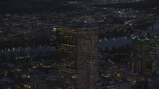 AX155_275 - 6K stock footage aerial video orbiting the top of US Bancorp Tower at night in Downtown Portland, Oregon