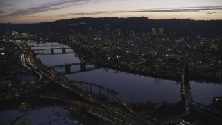 AX155_277 - 6K stock footage aerial video of the Willamette River, bridges and Downtown Portland, Oregon at twilight