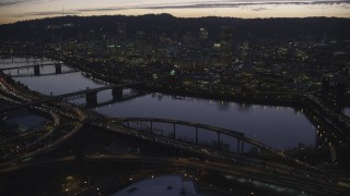 AX155_278 - 6K stock footage aerial video approaching freeway interchange, Willamette River, Burnside Bridge, and Downtown Portland, Oregon at twilight