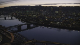 AX155_279 - 6K stock footage aerial video crossing the Willamette River to approach Burnside Bridge, White Stag sign, and Downtown Portland at twilight, Oregon