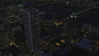AX155_289 - 6K stock footage aerial video flying away from Wells Fargo Center and KOIN Center near the river at night in Downtown Portland, Oregon
