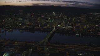 AX155_295 - 6K stock footage aerial video of Downtown skyscrapers, Morrison Bridge, and Willamette River at night, Downtown Portland, Oregon