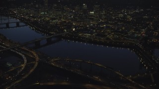 AX155_297 - 6K stock footage aerial video of Downtown skyscrapers, Willamette River bridges, freeway interchange, and White Stag sign at night, Downtown Portland, Oregon